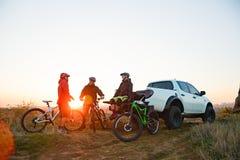 Amis se reposant près du camion d'Off Road de collecte après le vélo montant dans les montagnes au coucher du soleil Concept d'av images stock