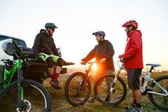 Amis se reposant près du camion d'Off Road de collecte après le vélo montant dans les montagnes au coucher du soleil Concept d'av images libres de droits