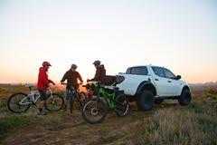 Amis se reposant près du camion d'Off Road de collecte après le vélo montant dans les montagnes au coucher du soleil Concept d'av photographie stock