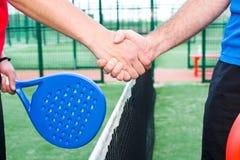 Amis se serrant la main dans le tennis de palette Photographie stock libre de droits