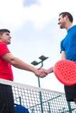 Amis se serrant la main dans le tennis de palette Photos stock