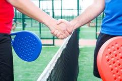 Amis se serrant la main dans le tennis de palette Image stock