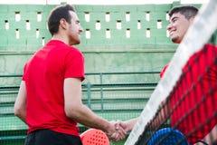 Amis se serrant la main dans le tennis de palette Images stock