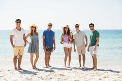 Amis se tenant à la plage pendant le jour ensoleillé Image libre de droits