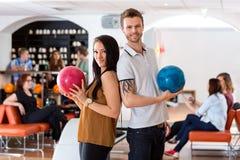 Amis se tenant ainsi que des boules de bowling dedans Photographie stock libre de droits