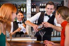 Amis se tenant au compteur tandis que barman préparant une boisson Images libres de droits