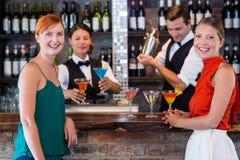 Amis se tenant au compteur tandis que barman préparant une boisson Photo libre de droits