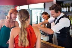 Amis se tenant au compteur tandis que barman préparant une boisson Images stock