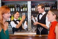 Amis se tenant au compteur tandis que barman préparant une boisson Image stock