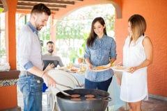 Amis se tenant au gril dans un barbecue Image libre de droits