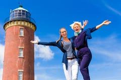 Amis se tenant au phare sur l'océan Images stock