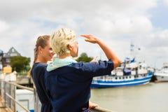 Amis se tenant au pilier de port regardant des bateaux Photo libre de droits