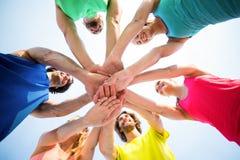 Amis se tenant avec les mains empilées contre le ciel Images libres de droits