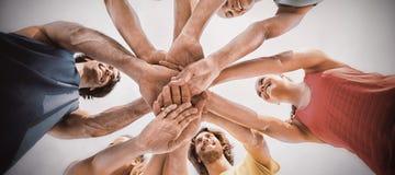 Amis se tenant avec les mains empilées contre le ciel Photographie stock libre de droits