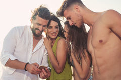 Amis se tenant ensemble et ayant l'amusement sur la plage Photo stock