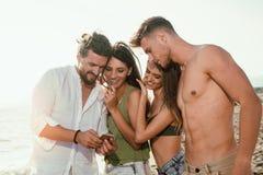 Amis se tenant ensemble et ayant l'amusement sur la plage u Photo stock