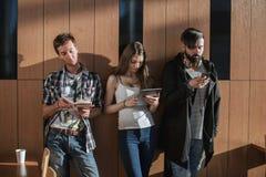 Amis se tenant près du mur avec des instruments dans leurs mains Image libre de droits