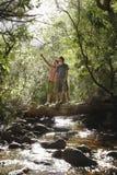 Amis se tenant sur le rondin au-dessus de Forest Stream Image stock