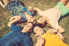 Amis se trouvant et détendant sur l'herbe Images stock