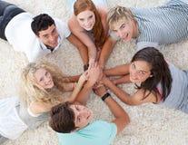 Amis se trouvant sur l'étage avec des mains ensemble Photographie stock libre de droits
