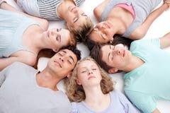 Amis se trouvant sur l'étage avec des têtes ensemble Image stock