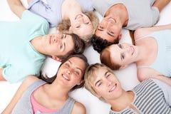 Amis se trouvant sur l'étage avec des têtes ensemble Photographie stock