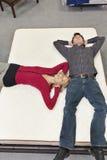 Amis se trouvant sur le matelas avec des mains derrière la tête dans le magasin de meubles Photo libre de droits