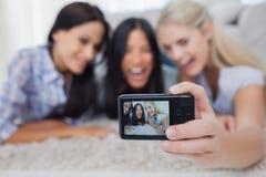 Amis se trouvant sur le plancher et prenant une photo d'individu Photos libres de droits
