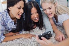 Amis se trouvant sur le plancher et regardant l'appareil photo numérique Images libres de droits
