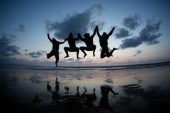 Amis silhouettés sautant dans le coucher du soleil à la plage Photos libres de droits