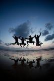 Amis silhouettés sautant dans le coucher du soleil à la plage Images stock