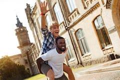 Amis sincères d'amusement ratant son coup autour au campus Photos stock