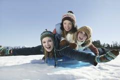 Amis Sledding à l'horaire d'hiver Photo stock