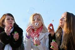 Amis soufflant des bulles dans la nature Photos stock