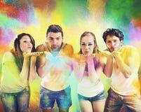 Amis soufflant les poudres colorées Image stock