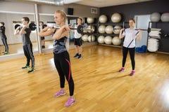 Amis soulevant des Barbells tout en se tenant dans le centre de fitness Photographie stock