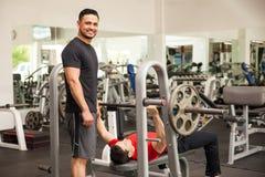 Amis soulevant des poids ensemble à un gymnase Photo stock