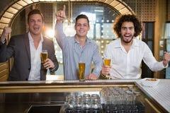 Amis soulevant leur poing tout en ayant la bière au compteur de barre Photographie stock