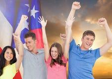 Amis soulevant leurs bras contre le coucher du soleil et le drapeau américain Images libres de droits