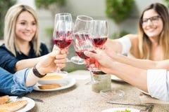 Amis soulevant leurs verres de vin pour un pain grillé Photographie stock libre de droits