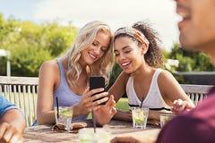 Amis souriant avec le smartphone Photos stock