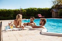 Amis souriant, cocktails potables, détente, se reposant près de la piscine Image libre de droits