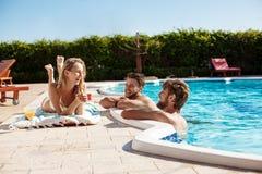 Amis souriant, cocktails potables, détente, se reposant près de la piscine Photos libres de droits