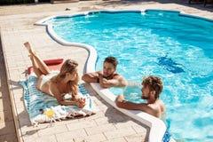 Amis souriant, cocktails potables, détente, se reposant près de la piscine Images stock