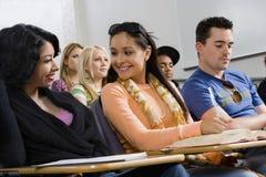 Amis souriant et regardant l'un l'autre dans la salle de classe Images stock