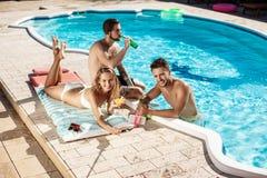Amis souriant, faisant le selfie, cocktails potables, détendant près de la piscine Photos libres de droits