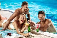 Amis souriant, faisant le selfie, cocktails potables, détendant près de la piscine Photos stock