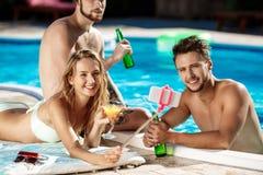 Amis souriant, faisant le selfie, cocktails potables, détendant près de la piscine Photographie stock