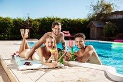 Amis souriant, faisant le selfie, cocktails potables, détendant près de la piscine Photo stock