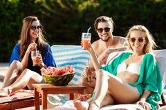 Amis souriant, mangeant la pastèque, cocktails potables, détendant près de la piscine Photo libre de droits